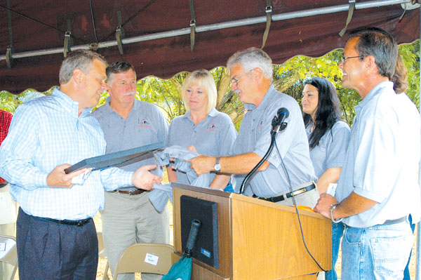 CV&T photo by Rhonda Smyth The Estill County Parks and Recreation Board presented a framed map of the park as it will look when it is finished and a parks and rec shirt to Fred Parker of Kentucky River Properties at a ribbon cutting ceremony last Friday. He was responsible for acquiring the donation of the land on which the new Kentucky River Park and Recreation Center is being built. Pictured are from left, Parker, and parks board members Mark Reese, Teresa Dawes, Scot Jones (president) Kim Dawes and Wallace Taylor. Not visible in the picture are Renee Alexander and Teresa Sparks.