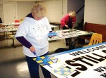 Arts council members paint new welcome signs