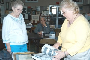 Florine Arthur, left and Ruth Horn look through one of the many books the Estill County Historical and Genealogical Society has published. Both women are officers in the society. In the background is board member, Norwood Thorpe.